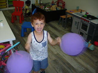 Child with balloons in Imagination Station